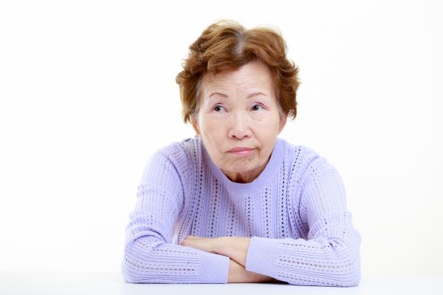 悩む高齢女性